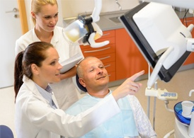 A middle-aged man looking at a screen while his dentist and dental assistant explain what they are looking at