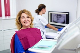 middle-aged woman smiling in dental chair