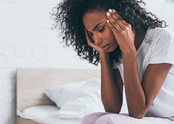 A young woman sitting on the side of her bed and holding her head because of an intense headache