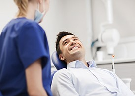 A male patient smiles at his dentist as she prepares to perform an oral cancer screening