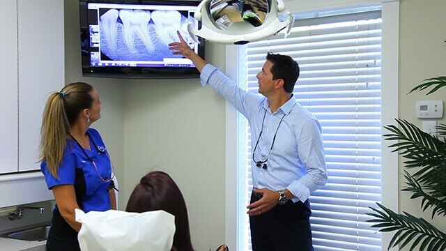 Dentist and patient in dental exam room