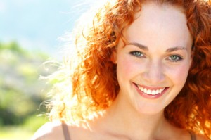 woman with a beautiful smile thanks to the cosmetic dentist palm beach gardens residents rely on