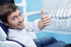 man smiling in his dental chair thanks to the jupiter dentist