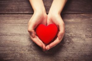 Outstretched hands holding heart for American Heart Health Month