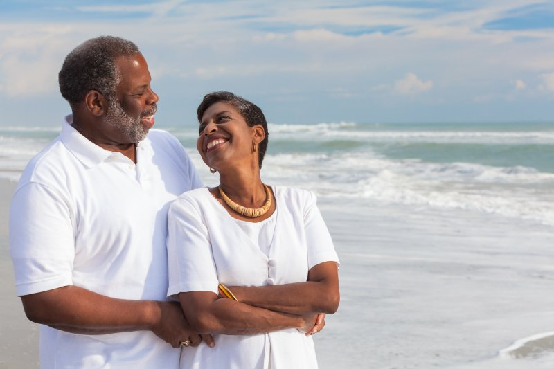 an older couple walking along the beach together after receiving dental implants in Juno Beach