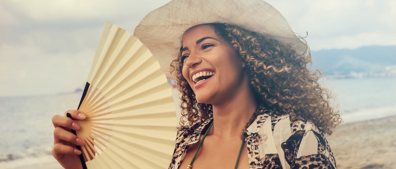 a young woman wearing a hat and carrying a hand fan while on the beach and showing off her beautiful smile