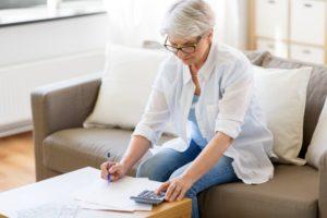 Senior woman looking at in-house dental savings plan paperwork